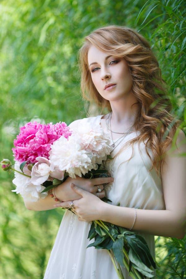 有牡丹花束的美丽的女孩在手上 免版税库存照片