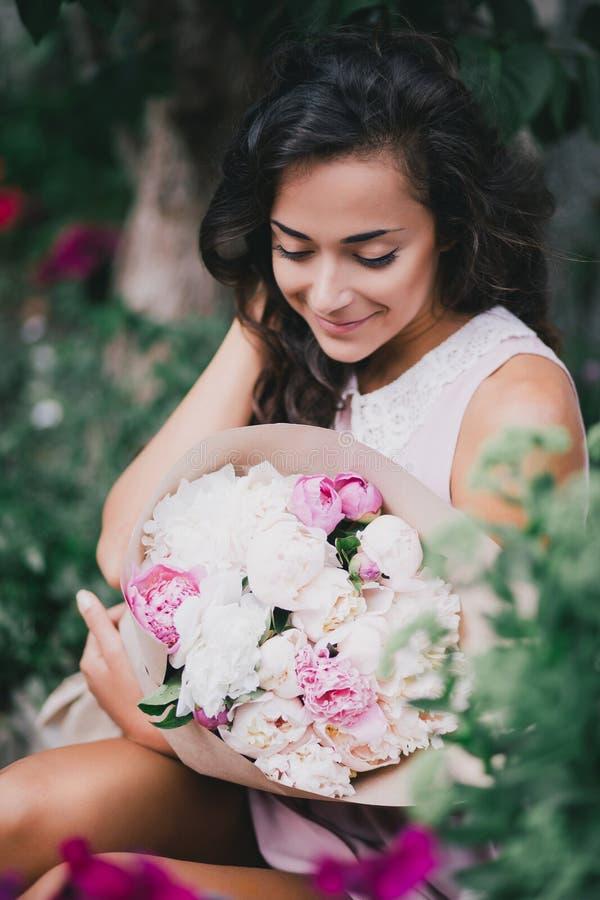 有牡丹花束的美丽的女孩  免版税库存图片