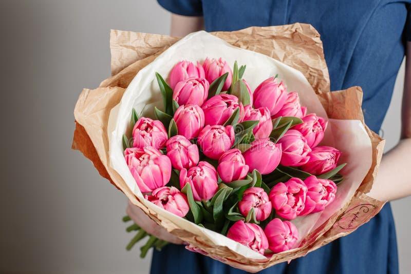 有牡丹花的卖花人女孩或桃红色郁金香少妇花花束为生日母亲节 免版税库存照片