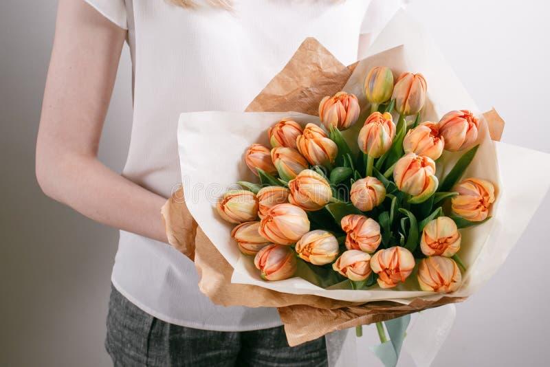 有牡丹花的卖花人女孩或橙色郁金香少妇花花束为生日母亲节 免版税库存图片
