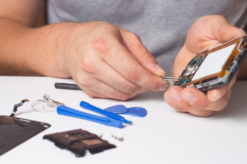 有特定工具和螺丝刀的安装工定象被拆卸的智能手机 电子修理设备的概念 库存图片