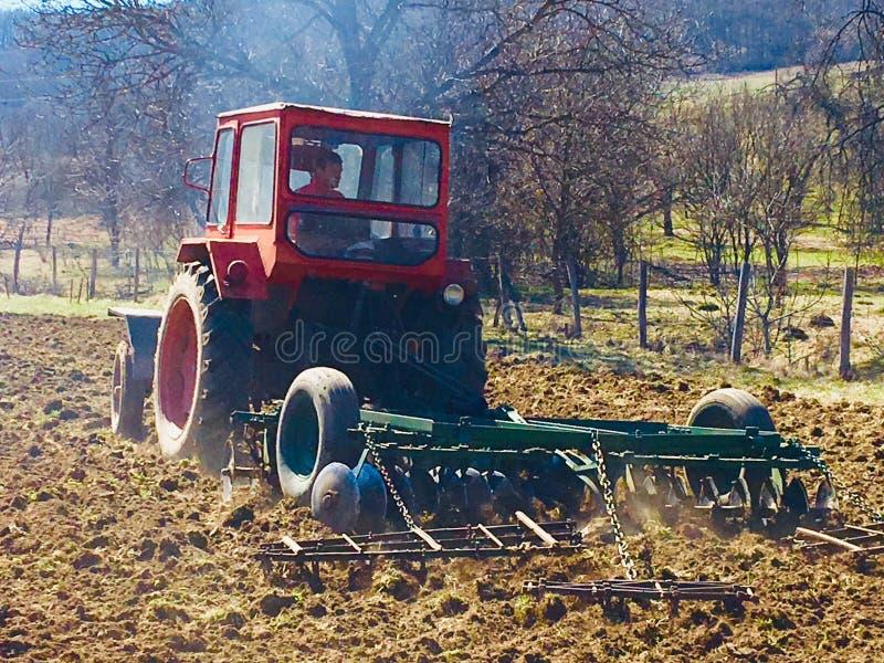 有犁土地的拖拉机的农夫 图库摄影