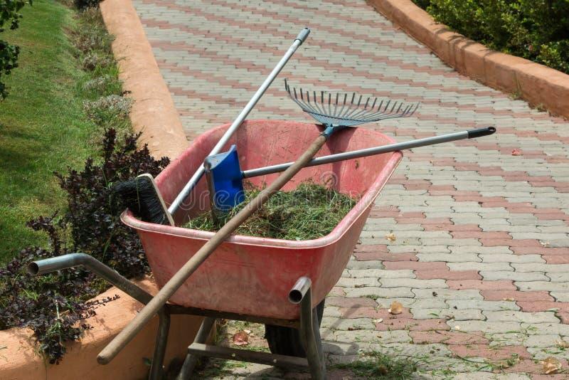有犁耙、笤帚和草的红色独轮车 库存图片