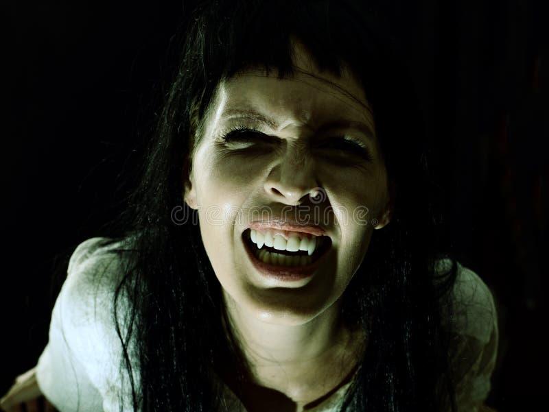 有犬齿的疯狂的血淋淋的可怕吸血鬼女孩 免版税库存图片
