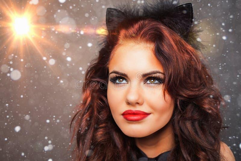 有狂欢节看星,圣诞夜的猫面具的妇女 库存照片