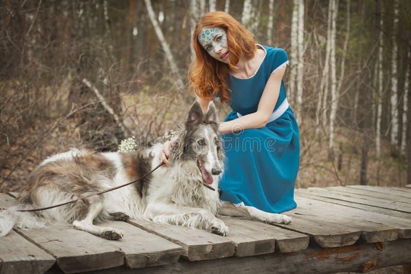 有狗的女孩在蓝色礼服在春天森林 免版税库存图片