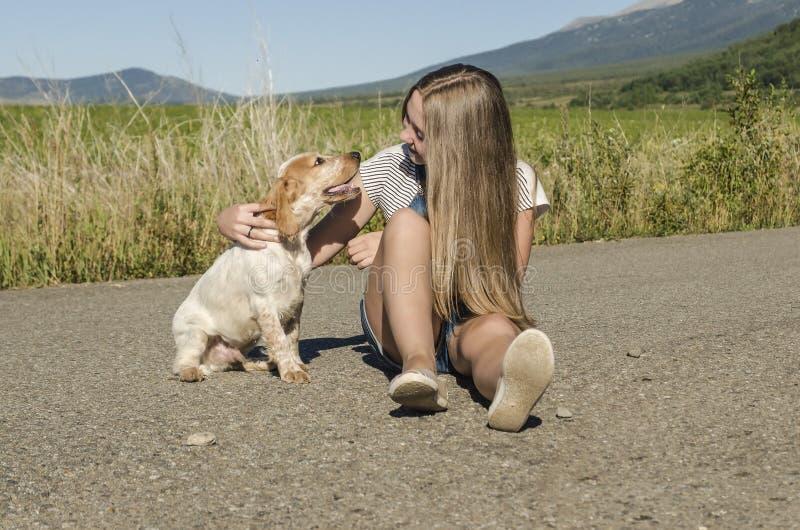 有狗的女孩坐路 库存图片