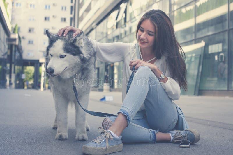 有狗的少妇在城市 有她的狗的少年女孩 免版税库存图片