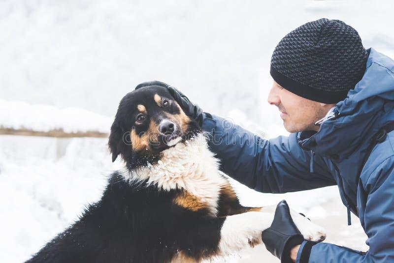 有狗的年轻人在雪 免版税库存图片