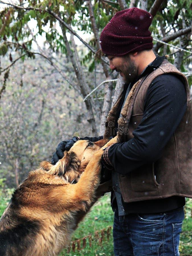 有狗的微笑的亚裔人 图库摄影