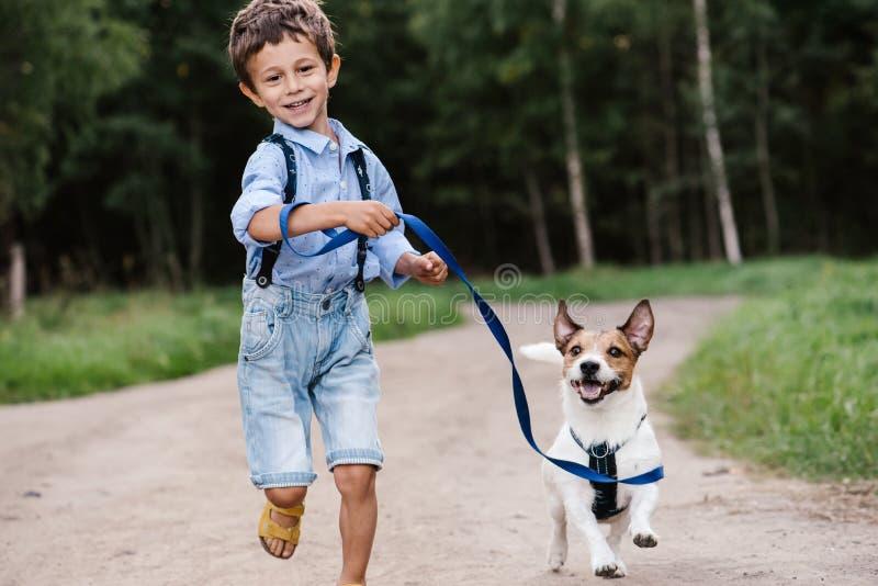 有狗的愉快的男孩在运行在乡下公路的皮带 库存照片