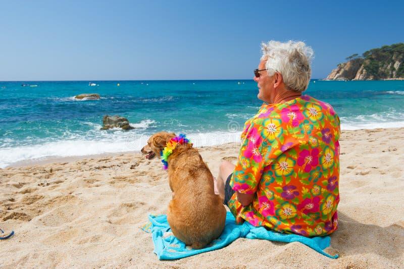有狗的老人在海滩 图库摄影