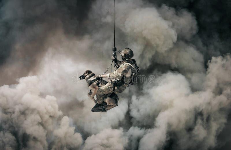 有狗系住的直升机的军事战士在烟之间 免版税库存图片