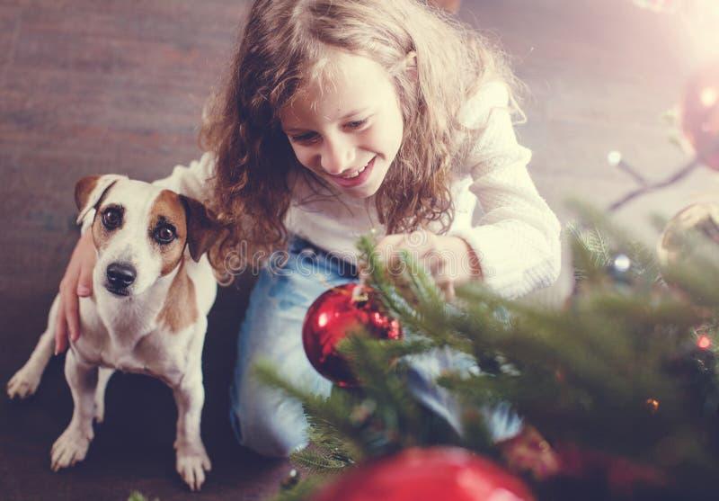 有狗装饰圣诞树的孩子 库存照片