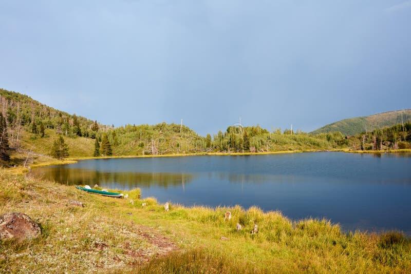 有独木舟的平静的农村湖在海岸线 免版税图库摄影