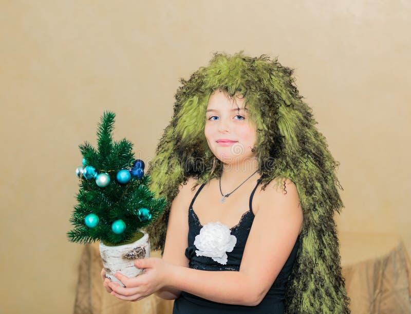 有独特的头发的微笑的美丽的小女孩削减了拿着小装饰的微型圣诞树 库存图片