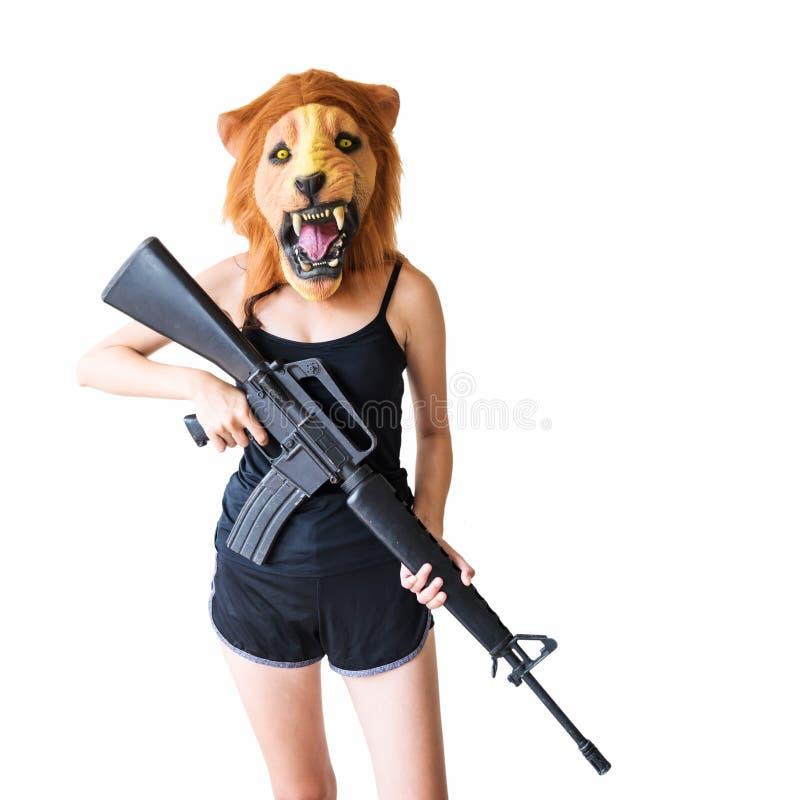 有狮子面具举行m16枪的妇女 库存照片