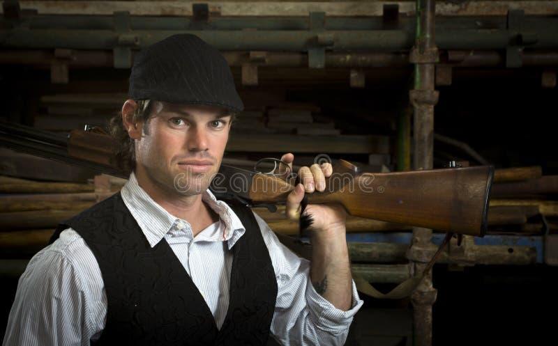 有猎枪的人在他的肩膀 免版税库存图片