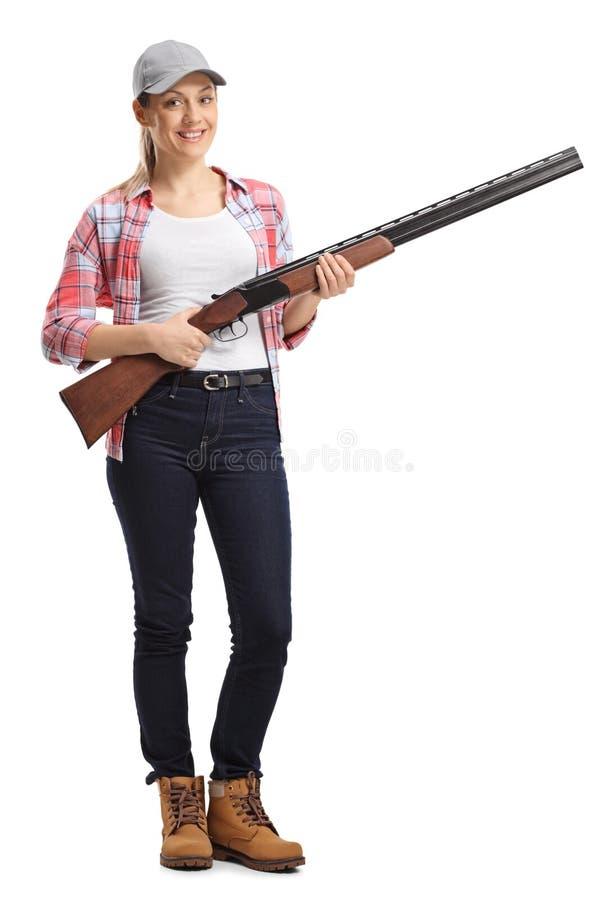 有猎枪的年轻女人 库存照片