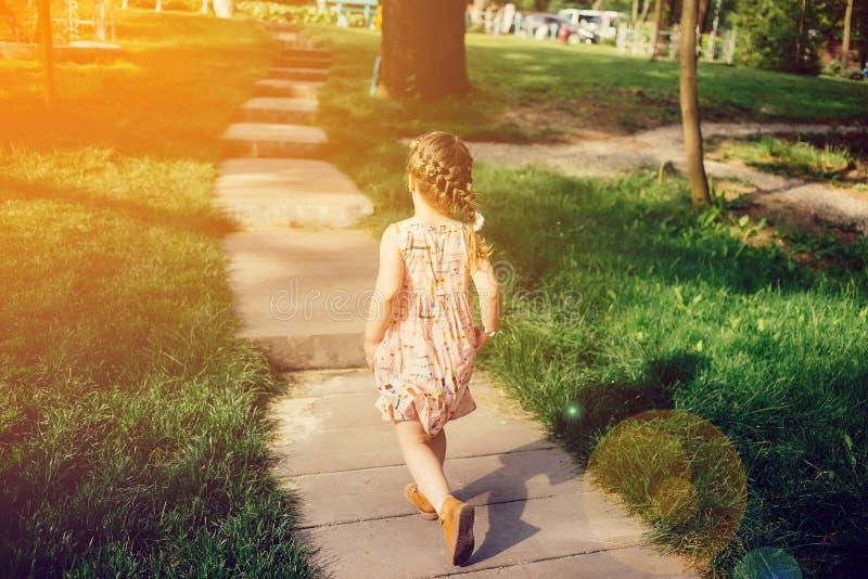 有猪尾的女孩在一件色的礼服在小径跑 图库摄影