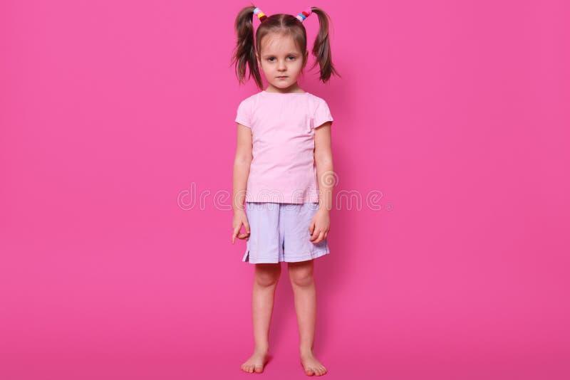 有猪尾的疲倦的磁性小女孩集中于照相机,看起来严肃,佩带的浅粉红色的T恤杉和偶然短裤,有 免版税图库摄影