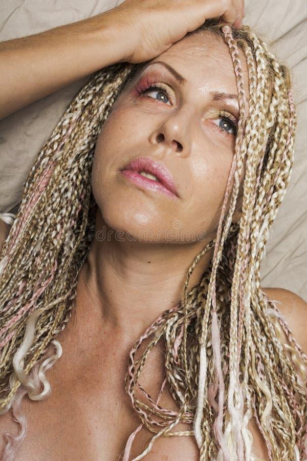 有猪尾的白肤金发的妇女 库存图片
