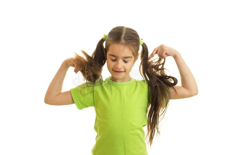有猪尾的滑稽的小女孩在绿色衬衣 库存图片