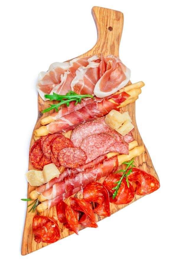 有猪排、熏火腿、蒜味咸腊肠和面包条的冷的熏制的肉板材 图库摄影