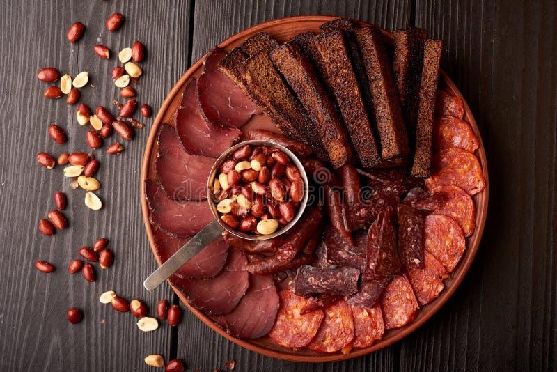 有猪排的冷的熏制的肉板材、熏火腿、蒜味咸腊肠和面包条和坚果在黑木背景 免版税库存照片