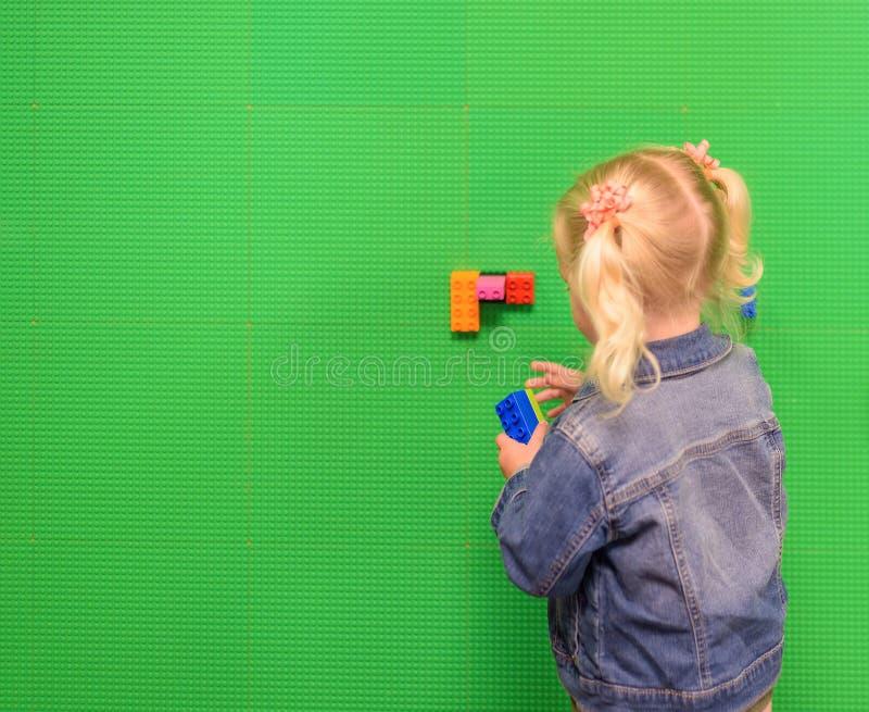 有猪的小女孩在图书馆盯梢使用与lego墙壁 库存图片