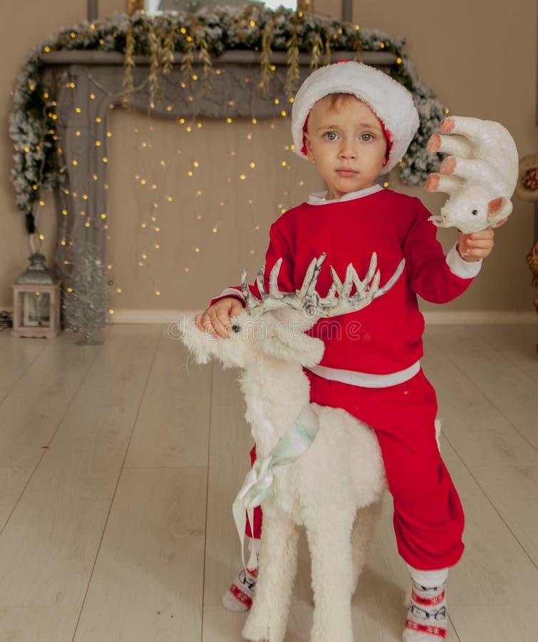 有猪的逗人喜爱的男孩坐在一张新年的carousell,新年的和圣诞节照片的装饰鹿 免版税库存照片