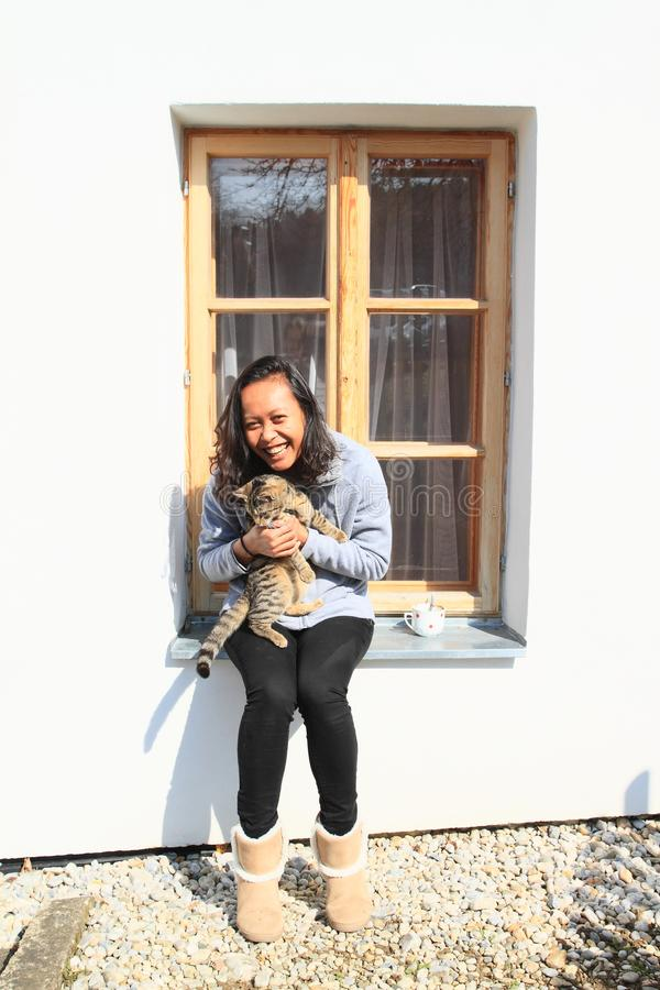 有猫的微笑的热带女孩在窗台 库存照片