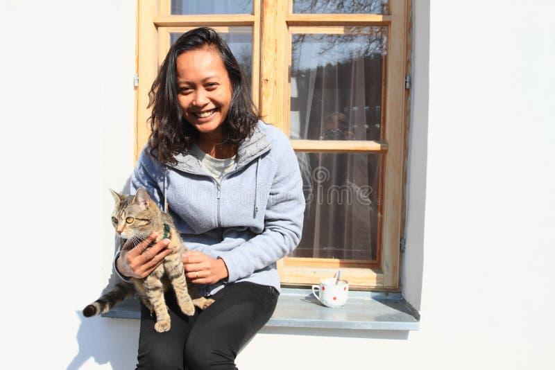 有猫的微笑的热带女孩在窗台 免版税库存照片