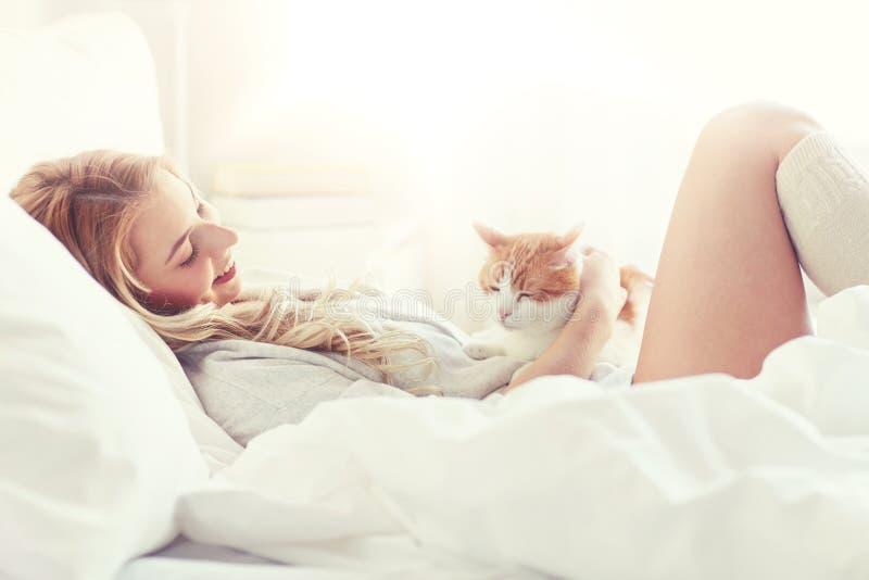 有猫的愉快的少妇在床上在家 免版税库存图片