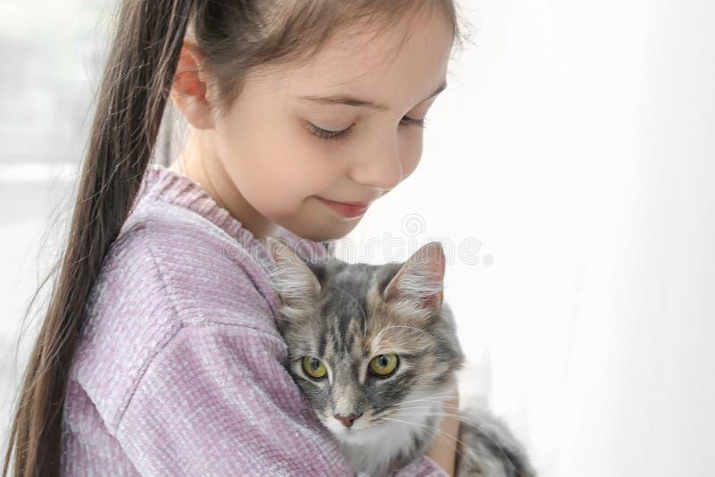 有猫的逗人喜爱的小女孩在窗口附近 免版税库存图片