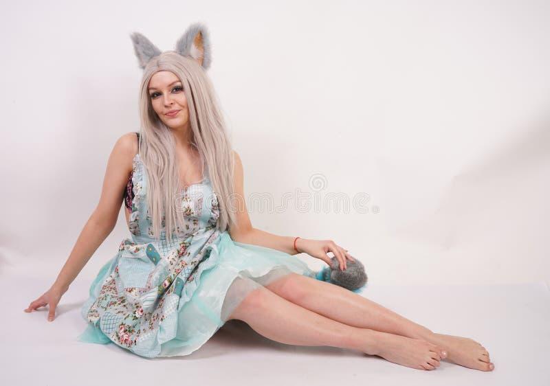 有猫耳朵的俏丽的嬉戏的少女和长的蓬松在被隔绝的白色背景的毛皮尾巴佩带的厨房围裙 库存照片
