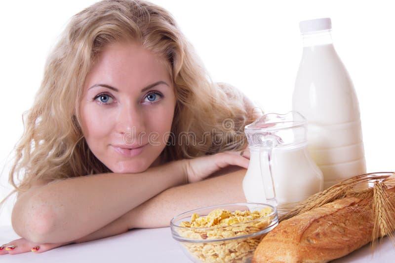 有玉米片和牛奶的妇女 免版税库存照片