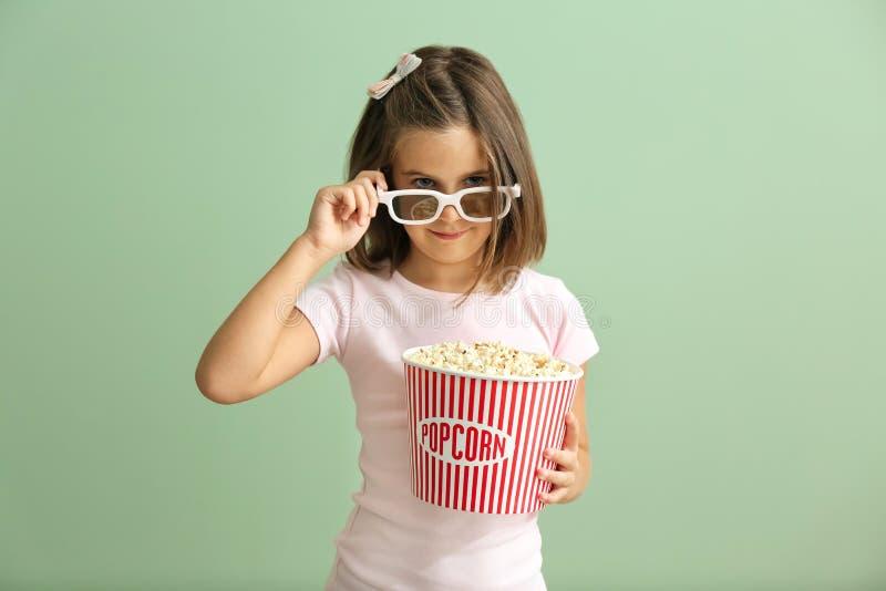 有玉米花戴3D在颜色背景的杯子的逗人喜爱的女孩戏院眼镜 免版税图库摄影