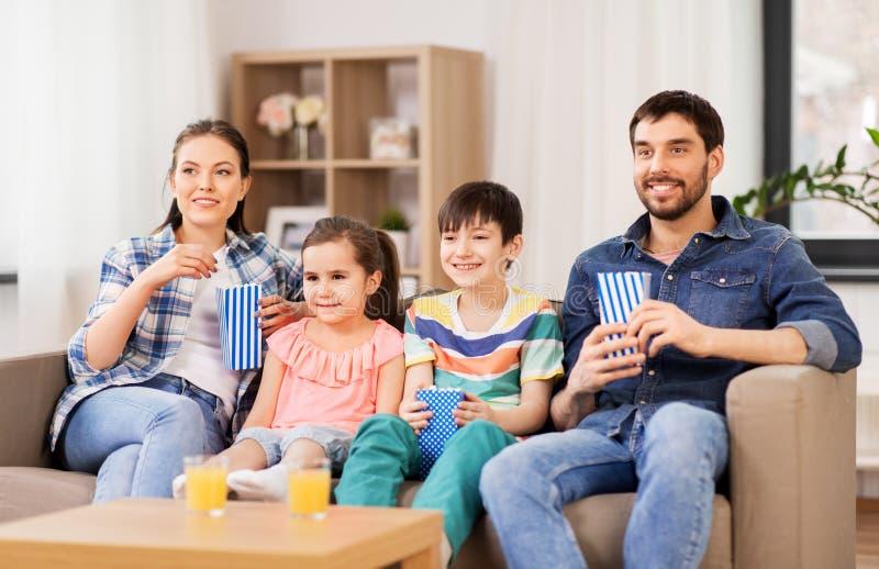 有玉米花看着电视的幸福家庭在家 图库摄影