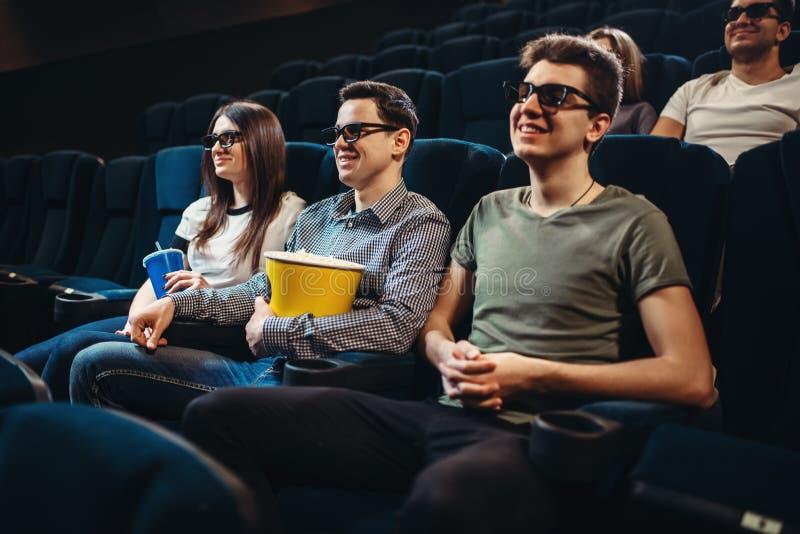 有玉米花观看的电影的人们在戏院 免版税库存图片