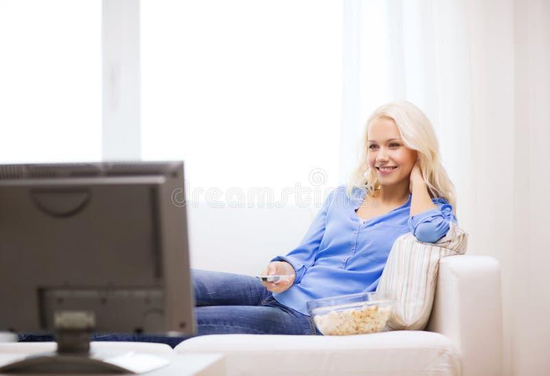 有玉米花观看的电影的女孩在家 库存照片