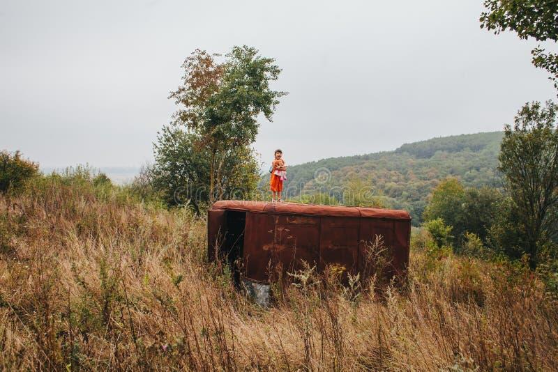 有玩偶的小女孩在老拖车站立在森林 免版税库存照片