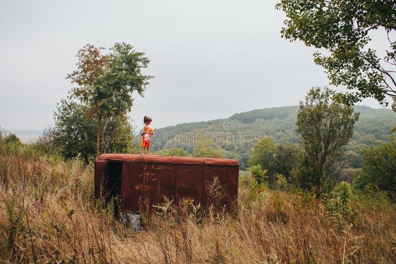 有玩偶的小女孩在老拖车站立在森林 库存图片