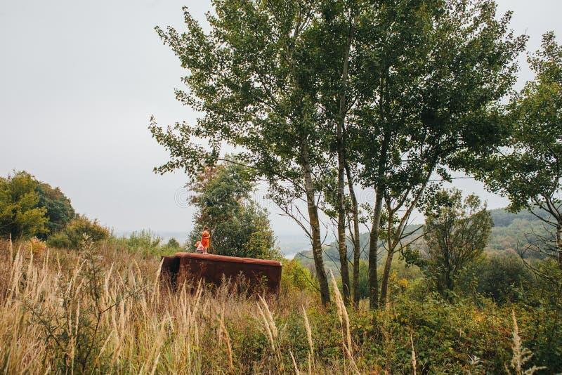 有玩偶的小女孩在老拖车站立在森林 免版税库存图片