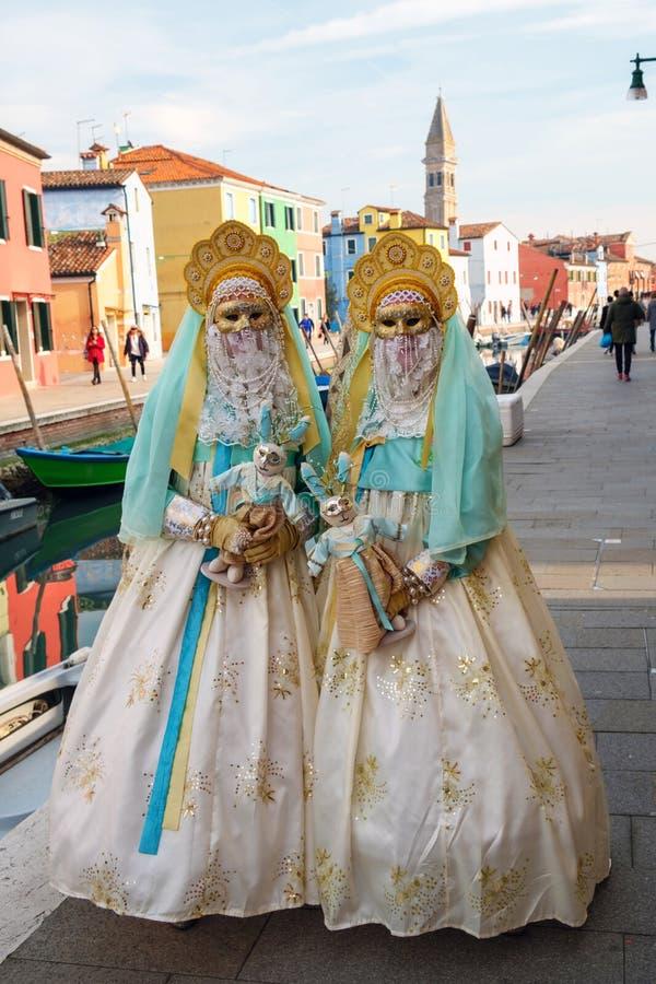 有玩偶的被掩没的妇女在摆在街道,威尼斯,意大利上的礼服 免版税库存图片