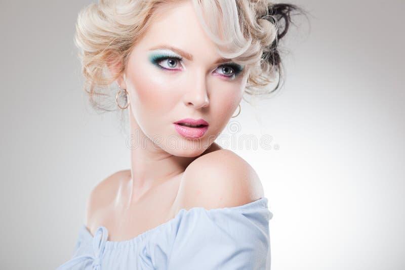 有玩偶表面佩带的构成的美丽的妇女 免版税库存照片