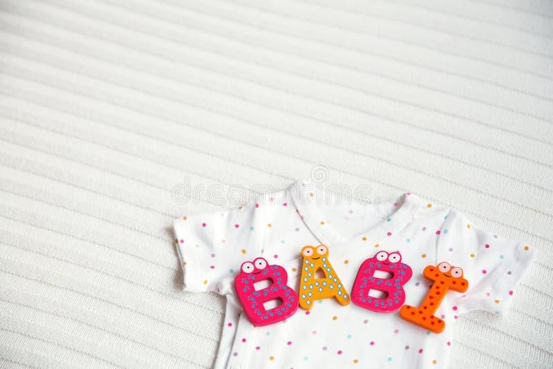 有玩具信件的-婴孩婴孩衣裳 免版税库存图片