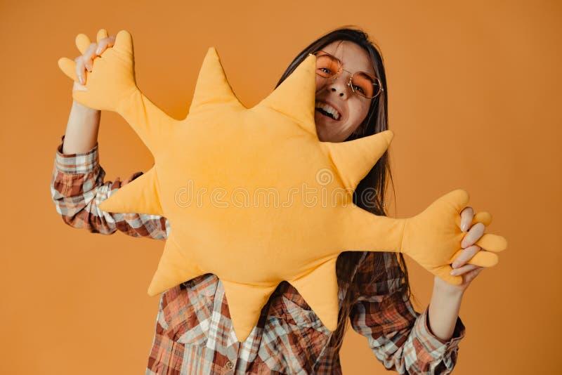 有玩具太阳的年轻白种人深色的女孩在橙色背景 免版税库存图片