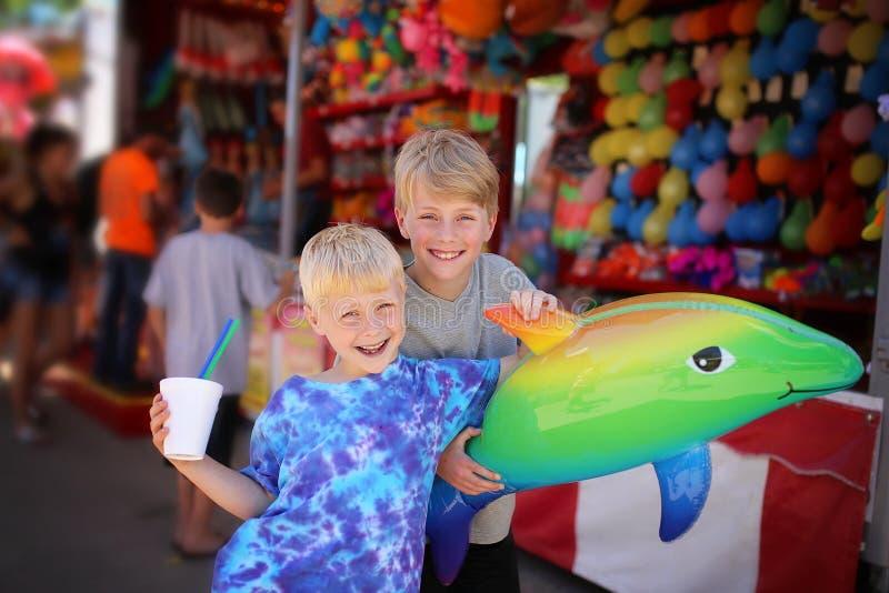 有玩具奖的两个愉快的孩子在小镇美国狂欢节 免版税库存照片