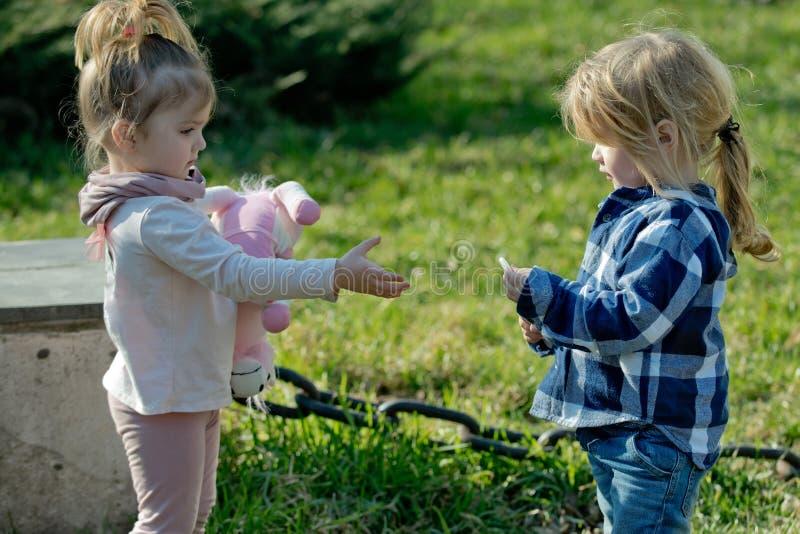 有玩具戏剧的女孩与自然本底的男孩 库存图片
